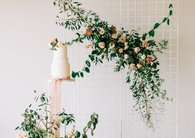 green and peach florals next to a simple white wedding cake