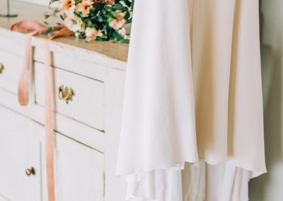 simple backless wedding gown hanging on a white vintage dresser