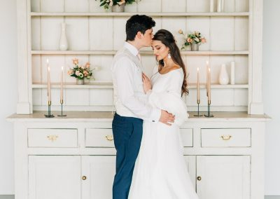 bride and groom standing in front of a white dresser