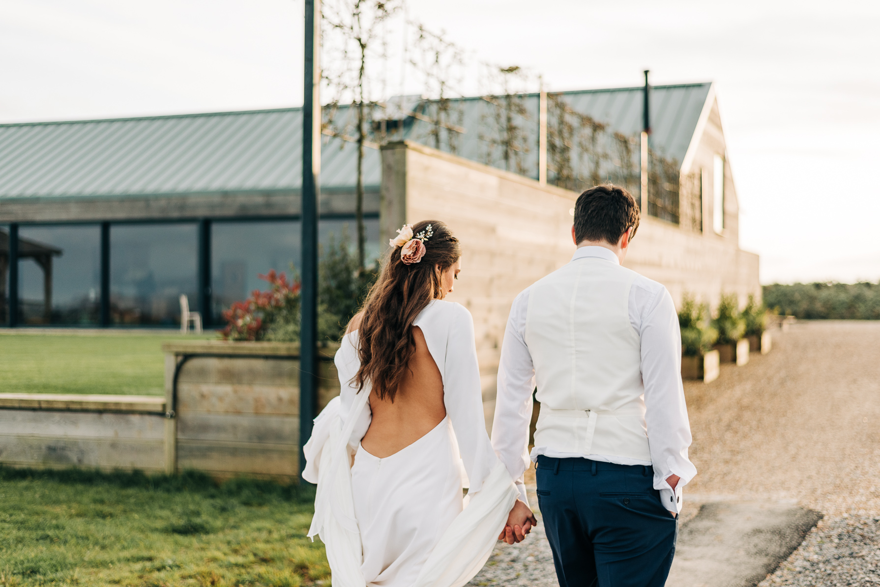 bride and groom walking hand in hand in sunset