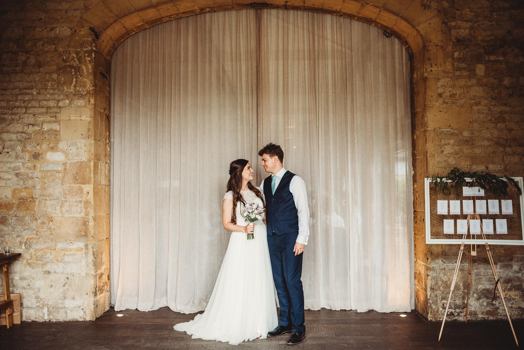 couple stood side by side by the arch at Lapstone barn