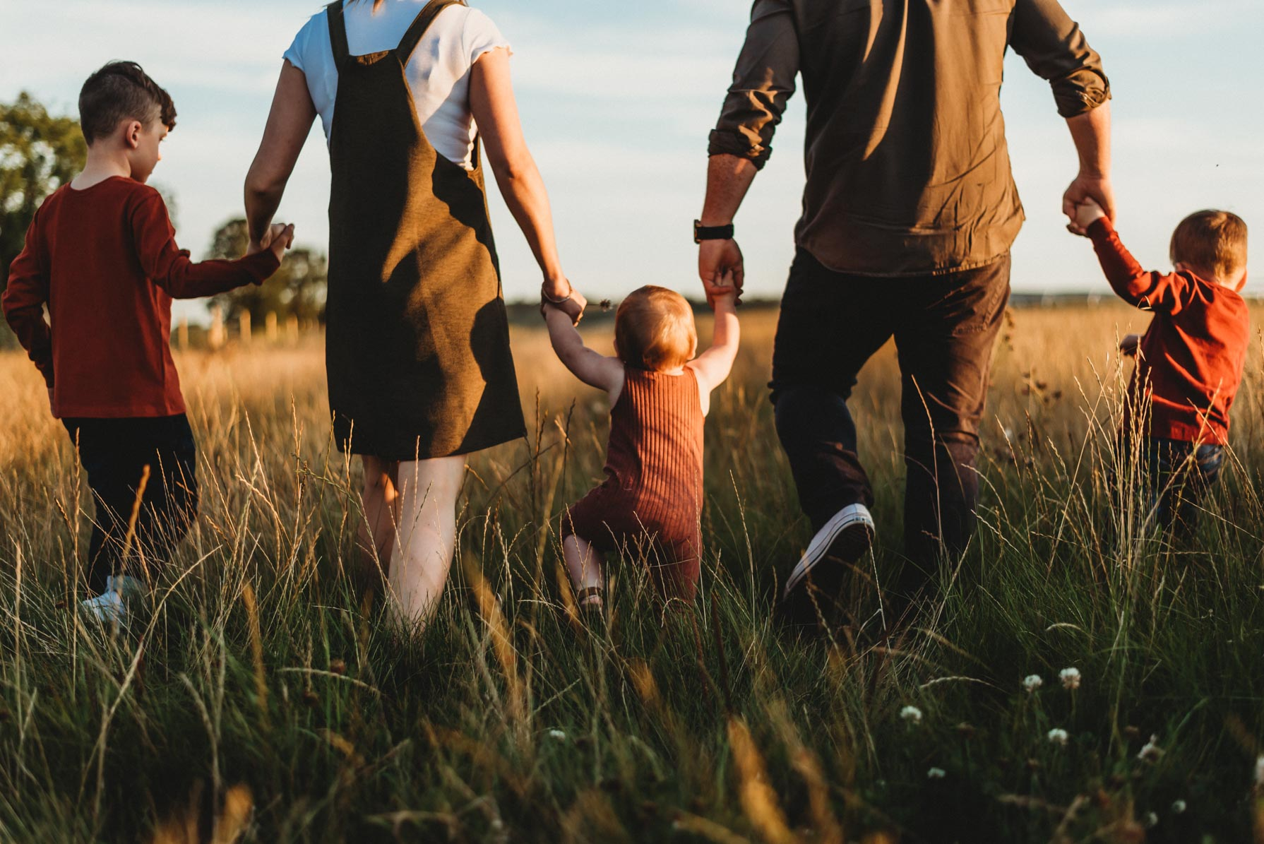 family of 5 walking hand in hand during sunset