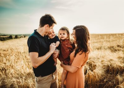 family photoshoot during sunset. Family of 4 standing together in a field of crops with the sun setting behind them