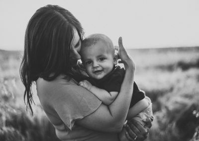 black and white photo of a mother holding her baby sun in a field