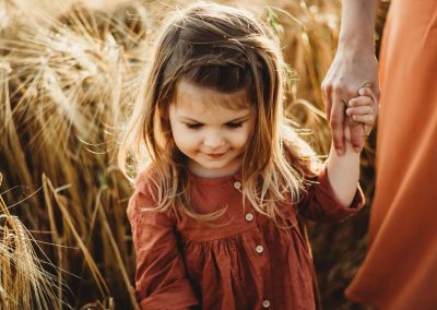 little girl in a red dress holding her mothers hand in a golden field