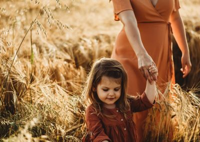 mother and daughter walking hand in hand through a field of golden crops