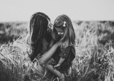 black and white images of a mother holding her little girl in a crop field
