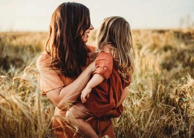 a little girl and her mum playing in a field of golden crops