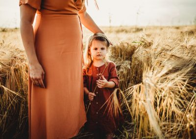 mother and daughter standing in a field of crops during sunset