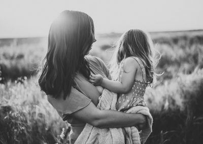 mother cuddling her little girl during a sunset