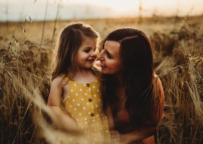 mother and daughter sitting in a golden field of crops