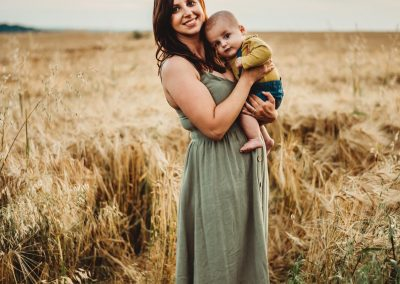 mother wearing a long green dress holding her baby boy in a field of golden crops