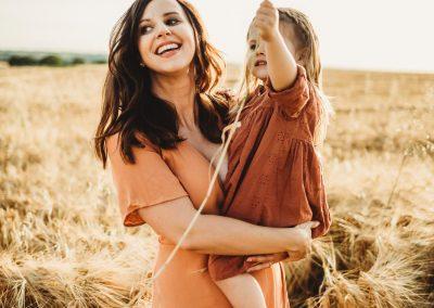 a mum wearing an orange dress holding her little girl