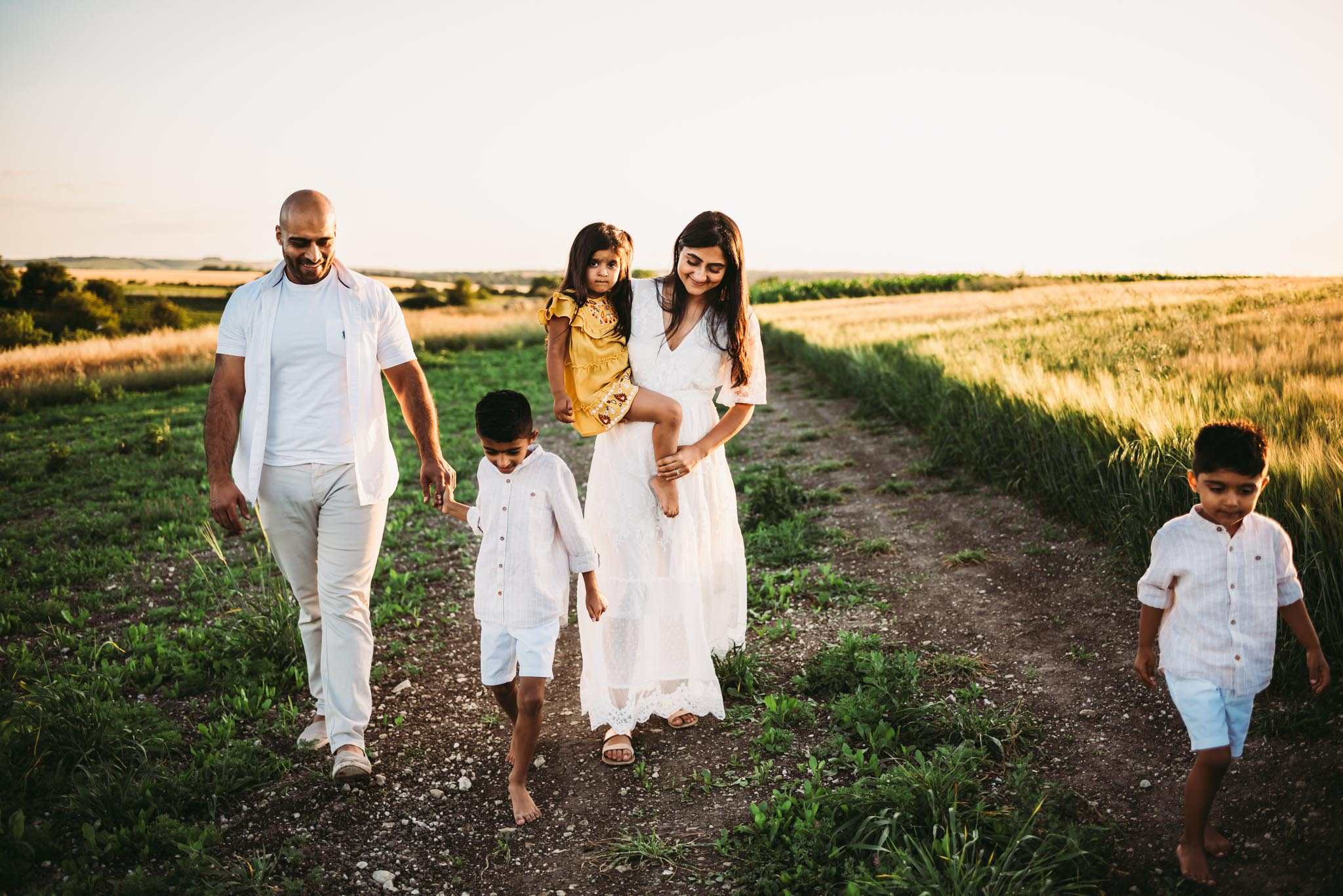 family of 5 walking hand in hand near a barley field during sunset