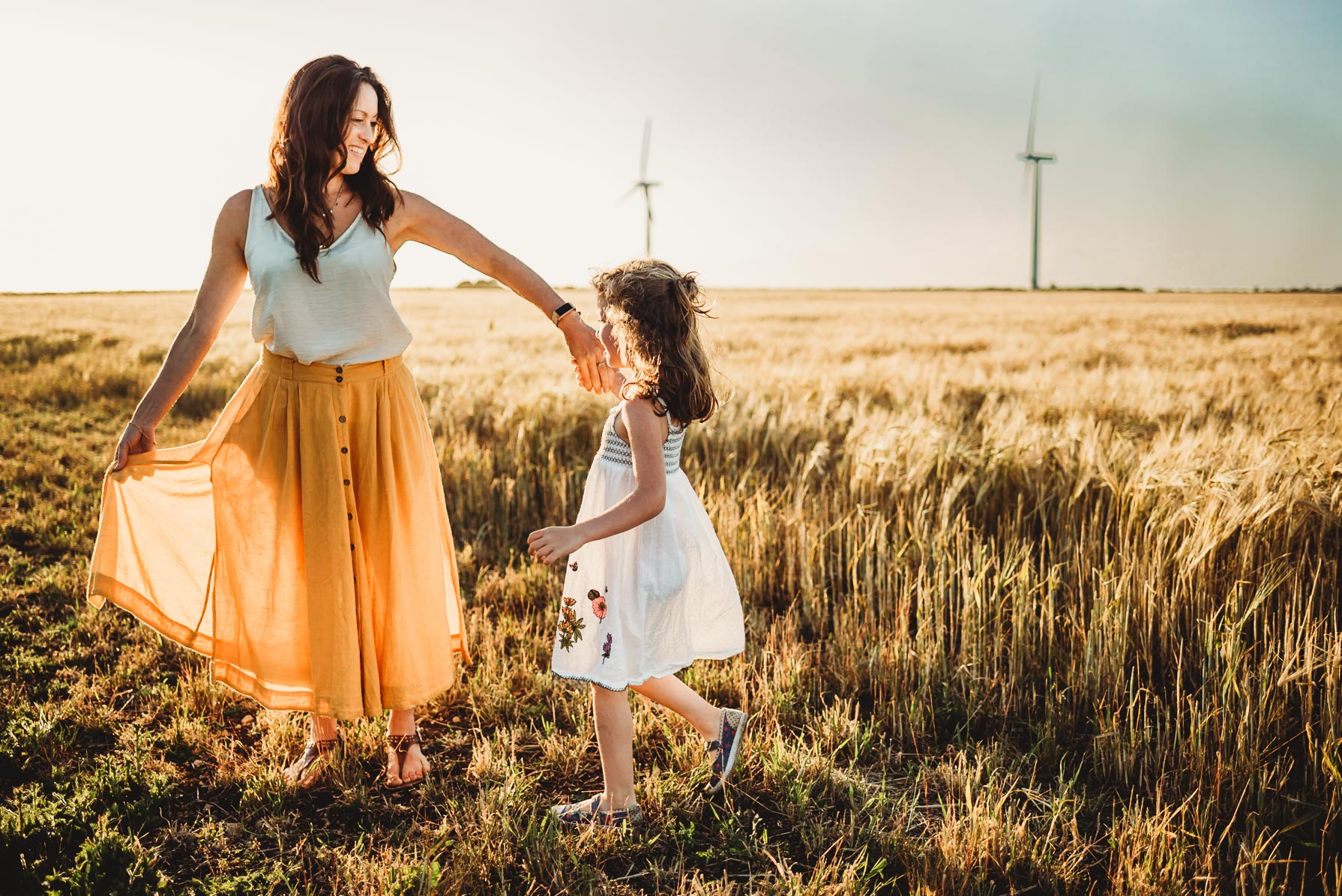 mother twirling with her little girl near a golden field with wind turbines in the back ground