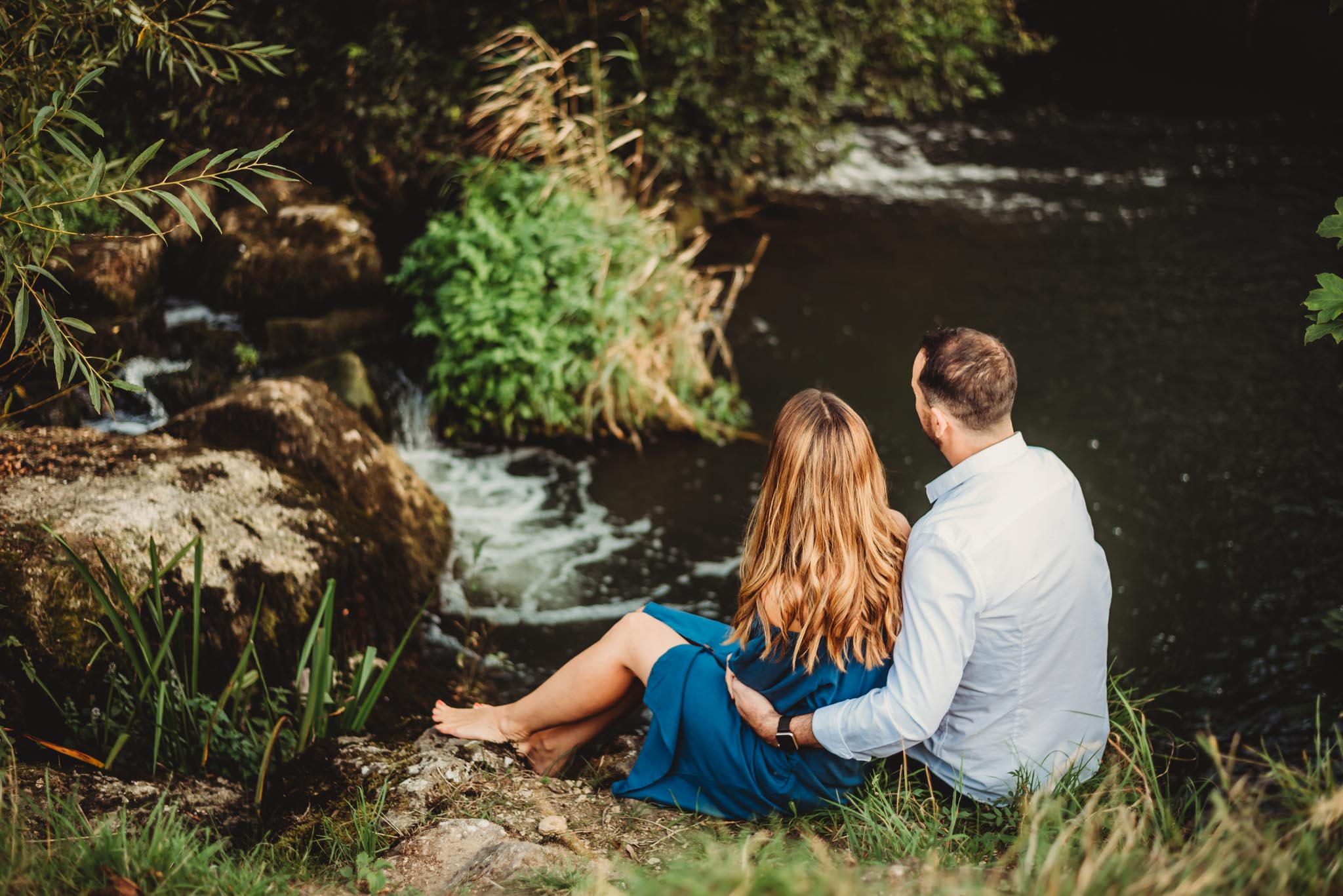 mum and dad sitting on rocks at the edge of the river watching their two boys play in the waterfall