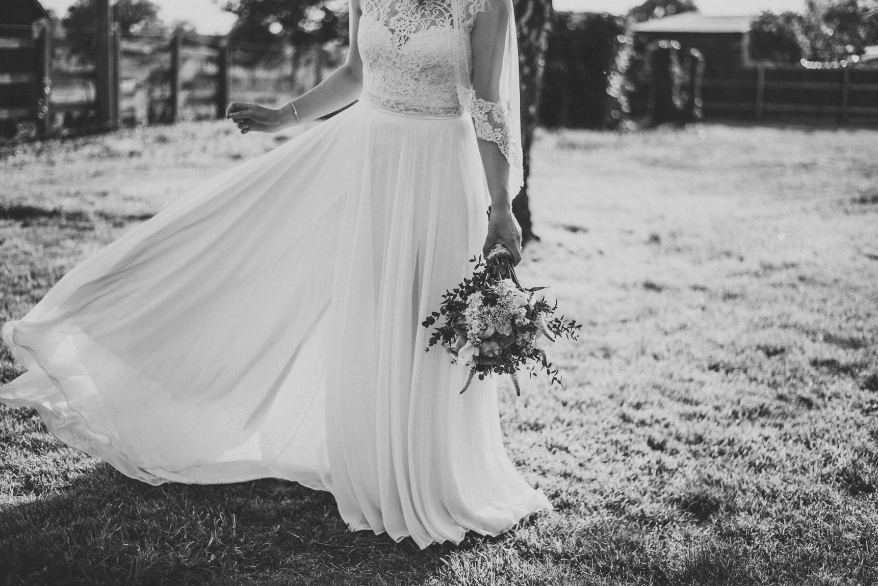 black and white image of a bride twirling in her wedding dress on the grass