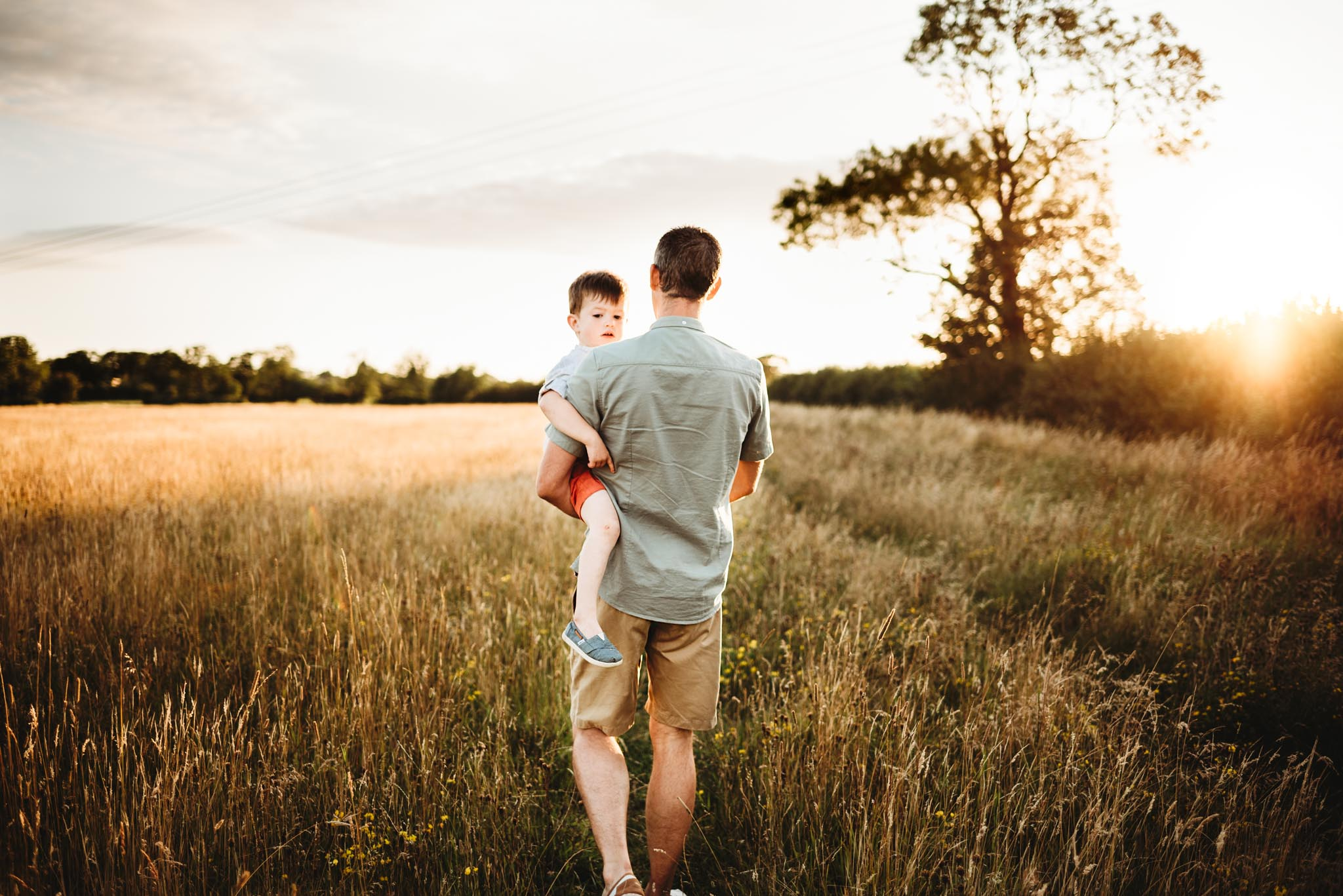 a man carrying his son in a field during sunset